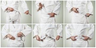 Judoka tying the white belt (obi) Royalty Free Stock Photography