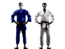 Judokas fighters fighting men silhouettes Stock Image