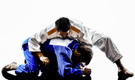 Judokas fighters fighting men silhouettes Royalty Free Stock Photos