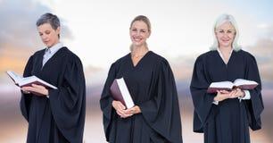 Jueces de las mujeres que sostienen los libros delante de las nubes del cielo Foto de archivo