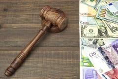 Jueces o subastadores mazo, dólares, euro, libras en la tabla de madera Imágenes de archivo libres de regalías