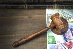 Jueces o subastadores mazo, dólares, euro, libras en la tabla de madera Fotos de archivo libres de regalías