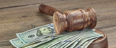 Jueces o subastadores mazo y pila del dinero en fondo de madera Fotos de archivo libres de regalías
