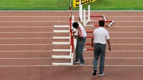 Jueces que arreglan obstáculos antes de la competencia final en los campeonatos del mundo de IAAF en Pekín, China Fotografía de archivo libre de regalías