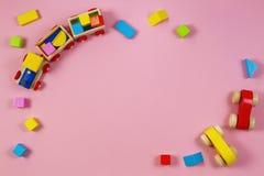 Juega el marco del fondo Tren y coches de madera del juguete con los bloques coloridos en fondo rosado imagen de archivo