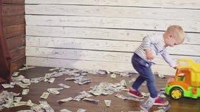 Juegan al muchacho con un coche del juguete en el piso, donde mucho dinero Concepto de riqueza almacen de video