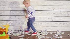 Juegan al muchacho con un coche del juguete en el piso, donde mucho dinero Concepto de riqueza almacen de metraje de vídeo