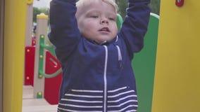 Juegan al muchacho en un patio en un parque o una guardería El niño es diversión a divertirse almacen de video