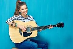 Juego adolescente de la muchacha con la diversión en la guitarra Foto de archivo libre de regalías