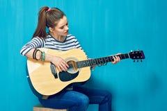 Juego adolescente de la muchacha con la diversión en la guitarra Fotografía de archivo