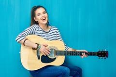 Juego adolescente de la muchacha con la diversión en la guitarra Imagen de archivo libre de regalías
