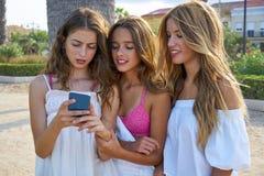 Juego adolescente de las muchachas de los mejores amigos con smartphone Fotos de archivo libres de regalías