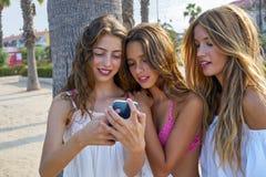 Juego adolescente de las muchachas de los mejores amigos con smartphone Imagen de archivo