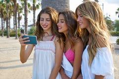 Juego adolescente de las muchachas de los mejores amigos con smartphone Foto de archivo libre de regalías
