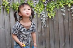 Juego adorable precioso travieso lindo de la muchacha del niño de Aisa con la cámara del beso del globo al aire libre en niñez fe Imagenes de archivo