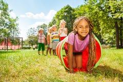 Juego africano de la muchacha que se arrastra a través del tubo en parque Foto de archivo libre de regalías