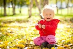 Juego alegre del bebé con la ramificación de madera en parque Foto de archivo libre de regalías
