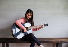 Juego asiático de la mujer con la guitarra Foto de archivo