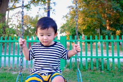 Juego asiático joven del muchacho un hierro que balancea en el patio debajo de Foto de archivo libre de regalías