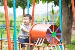 Juego asiático joven del muchacho un tren del hierro que balancea en el und del patio Foto de archivo