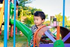 Juego asiático joven del muchacho un tren del hierro que balancea en el und del patio Foto de archivo libre de regalías