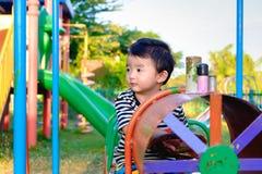 Juego asiático joven del muchacho un tren del hierro que balancea en el und del patio Imágenes de archivo libres de regalías