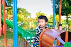 Juego asiático joven del muchacho un tren del hierro que balancea en el und del patio Imagenes de archivo