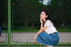 Juego chino asiático del estudiante universitario en el patio del campo de tenis Fotografía de archivo libre de regalías