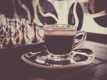 Juego de ajedrez a bordo y café caliente Imágenes de archivo libres de regalías