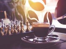 Juego de ajedrez a bordo y café caliente Imagen de archivo