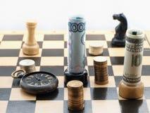 Juego de ajedrez con el dinero Imagenes de archivo