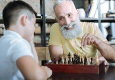 Juego de ajedrez de enseñanza del niño del abuelo pensativo fotografía de archivo
