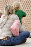 Juego de béisbol de observación de la mama y del bebé en líneas laterales Foto de archivo
