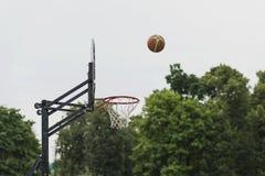 Juego de baloncesto de la calle Escudo, cesta y bola del baloncesto en el fondo del cielo, árboles, calle Concepto de deporte, ac Foto de archivo