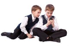 Juego de dos colegiales en el teléfono móvil Imagenes de archivo