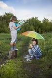 Juego de dos hermanos en lluvia al aire libre imagenes de archivo