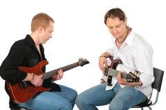 Juego de dos hombres que se sienta en las guitarras imagen de archivo libre de regalías