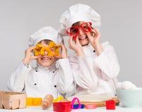 Juego de dos niños divertido en la cocina fotografía de archivo