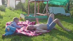 Juego de dos niños en el césped en un día de verano caliente Los niños ríen, corren y se caen en el césped Entretenimiento al air almacen de video