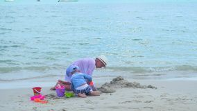 Juego de dos niños en una playa arenosa con los juguetes Isla tropical, día caliente almacen de metraje de vídeo