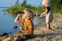 Juego de dos niños de los hermanos cerca del lago con los prismáticos Imagen de archivo libre de regalías