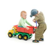 Juego de dos niños pequeños con el carro del juguete Fotos de archivo libres de regalías