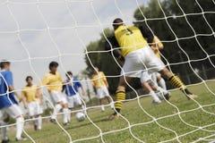 Juego de fútbol visto a través de red Imagen de archivo libre de regalías