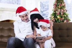 Juego de la familia de la Navidad con una tableta Fotos de archivo