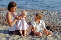 Juego de la familia en una playa Imagen de archivo libre de regalías
