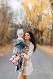 Juego de la mamá de la mujer joven con poca hija en el camino del parque del otoño foto de archivo libre de regalías