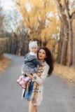 Juego de la mamá de la mujer joven con poca hija en el camino del parque del otoño imagen de archivo libre de regalías