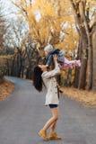 Juego de la mamá de la mujer joven con poca hija en el camino del parque del otoño fotografía de archivo libre de regalías