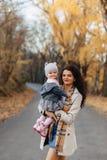Juego de la mamá de la mujer joven con poca hija en el camino del parque del otoño fotos de archivo libres de regalías