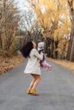 Juego de la mamá de la mujer joven con poca hija en el camino del parque del otoño imagen de archivo